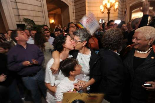 Sue Rochman, left, and Robin Romdalvik kiss, reacting to the U.S. Supreme Court's ruling on gay marriage in California, at San Francisco's City Hall on Wednesday, June 26, 2013. The couple is accompanied by their son Maddox Rochman-Romdalvik.  The justices issued two 5-4 rulings in their final session of the term. One decision wiped away part of a federal anti-gay marriage law that has kept legally married same-sex couples from receiving tax, health and pension benefits. The other was a technical legal ruling that said nothing at all about same-sex marriage, but left in place a trial court's declaration that California's Proposition 8 is unconstitutional. Photo: Noah Berger, Associated Press