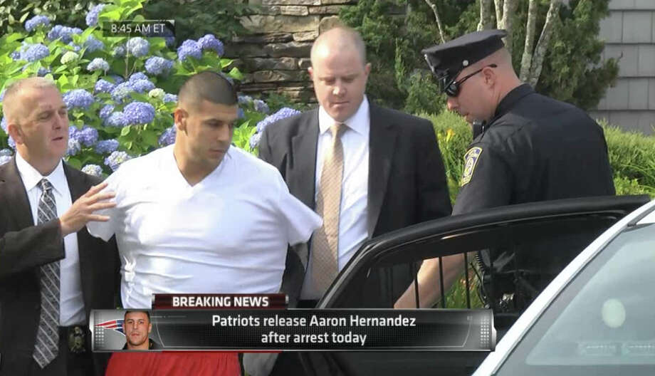 In this image taken from video, police escort Aaron Hernandez from his home in handcuffs in Attleboro, Mass., Wednesday, June 26, 2013. Hernandez was taken from his home more than a week after a Boston semi-pro football player was found dead in an industrial park a mile from Hernandez's house. (AP Photo/ESPN) Photo: Associated Press / ESPN