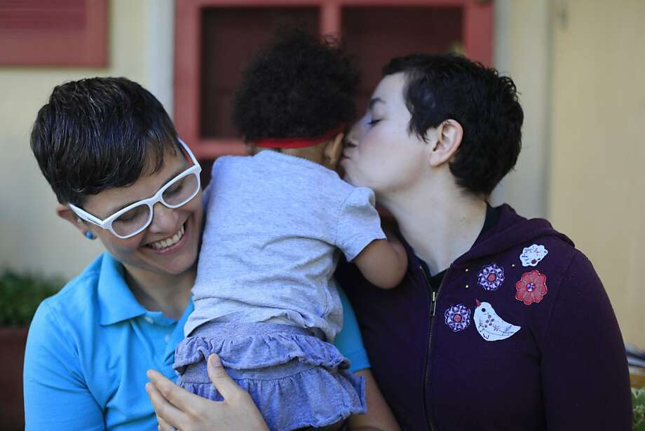 Same-sex partners of 10 years, Marlene White and Elana Metz, at home with their daughter Nia, hug and kiss after the Supreme Court of the United States both dismissed Proposition 8  and ruled the Defense of Marriage Act unconstitutional on the morning of Wednesday June 26, 2013 in Oakland, Calif. The couple said they are ready to get married again legally. Photo: Mike Kepka, The Chronicle