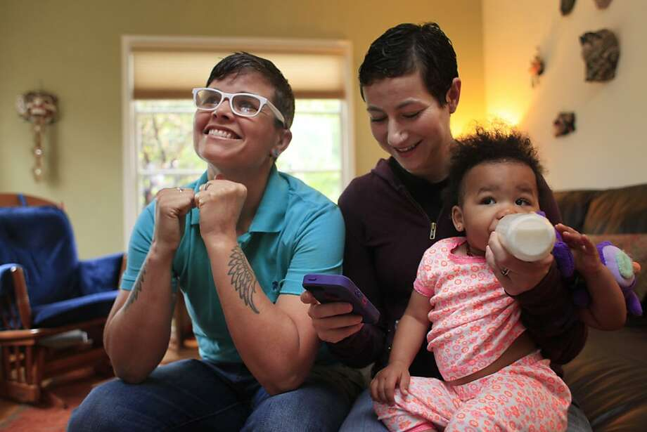 Marlene White (left) and Elana Metz, who've been together for a decade, watch with daughter Nia as the Supreme Court declares that they can make it legal. Photo: Mike Kepka, The Chronicle