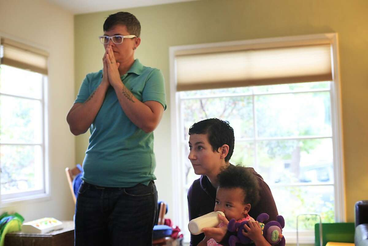 Same-sex partners of 10 years, Marlene White and Elana Metz, at home with their daughter Nia, nervously wait and watch television reports moments before the Supreme Court of the United States both dismissed Proposition 8 and ruled the Defense of Marriage Act unconstitutional on the morning of Wednesday June 26, 2013 in Oakland, Calif.