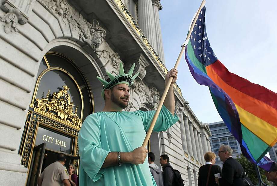 Nikolas Lemos shows his supports for gay rights on the steps of City Hall as he awaits the Supreme Court rulings in San Francisco, Calif. on Wednesday June 26, 2013, later handing down their decisions dismissing California's Proposition 8 and striking down parts of the Defense of Marriage Act. Photo: Michael Macor, The Chronicle