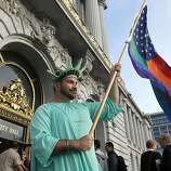 Nikolas Lemos shows his supports for gay rights on the steps of City Hall as he awaits the Supreme Court rulings in San Francisco, Calif. on Wednesday June 26, 2013, later handing down their decisions dismissing California's Proposition 8 and striking down parts of the Defense of Marriage Act.