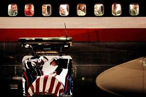 """When 2nd Lt. James Cathey's body arrived at the Reno Airport, Marines climbed into the cargo hold of the plane and draped the flag over his casket as passengers watched the family gather on the tarmac. During the arrival of another Marine's casket last year at Denver International Airport, Major Steve Beck described the scene as one of the most powerful in the process: """"See the people in the windows? They'll sit right there in the plane, watching those Marines. You gotta wonder what's going through their minds, knowing that they're on the plane that brought him home,"""" he said. """"They're going to remember being on that plane for the rest of their lives. They're going to remember bringing that Marine home. And they should."""" (TODD HEISLER/ROCKY MOUNTAIN NEWS)"""