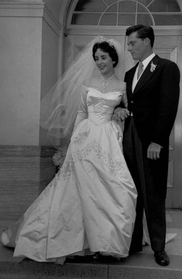 Actress Elizabeth Taylor, 18, wearing beautiful long satin wedding gown (cost $1,500, a gift from MGM studios) w. husband Nicky Hilton, 23, on steps of church after their wedding ceremony.  (Photo by Ed Clark//Time Life Pictures/Getty Images)