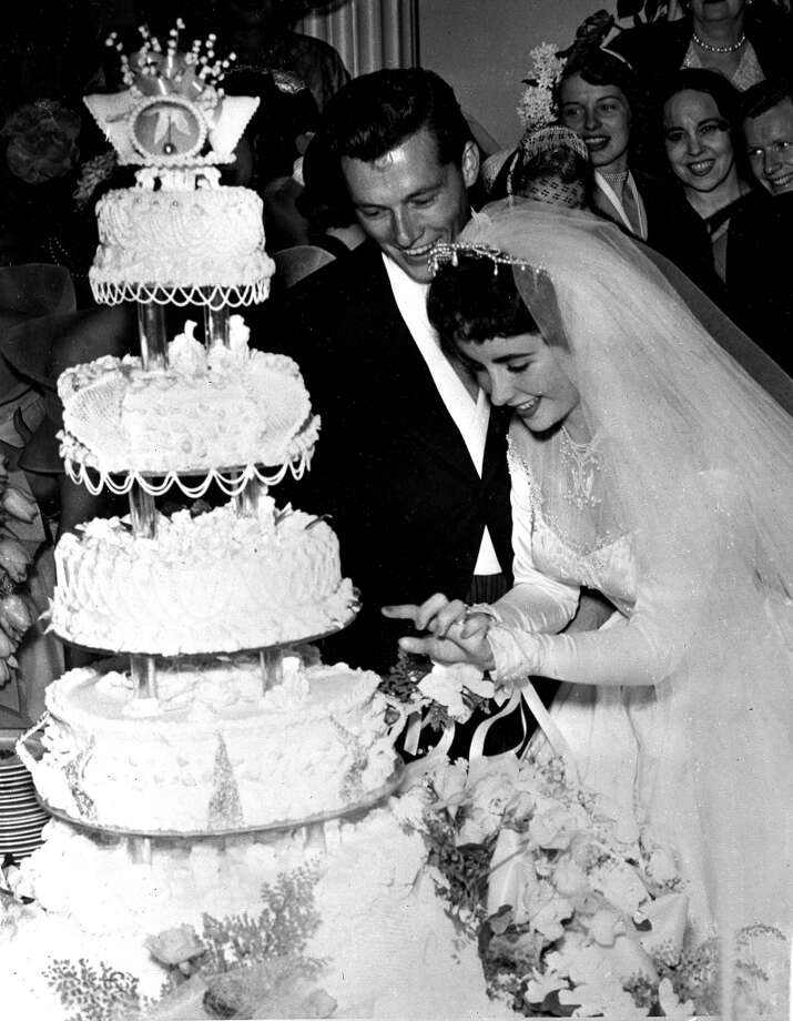 6th May 1950, Shown here are the newly wedded couple, Conrad Hilton Jnr, and his actress bride, Elizabeth Taylor, pictured cutting the cake at a huge reception at the Bel-Air Country Club, Hilton was the great-uncle of heiress and professional celebrity Paris Hilton. California, USA  (Photo by Popperfoto/Getty Images)