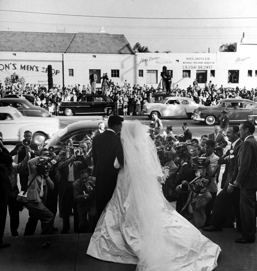 Actress Elizabeth Taylor wearing beautiful long satin wedding gown (cost $1,500, a gift from MGM studios) w. husband Nicky Hilton on steps of church, posing for an army of photographers after their wedding ceremony.  (Photo by Ed Clark//Time Life Pictures/Getty Images)