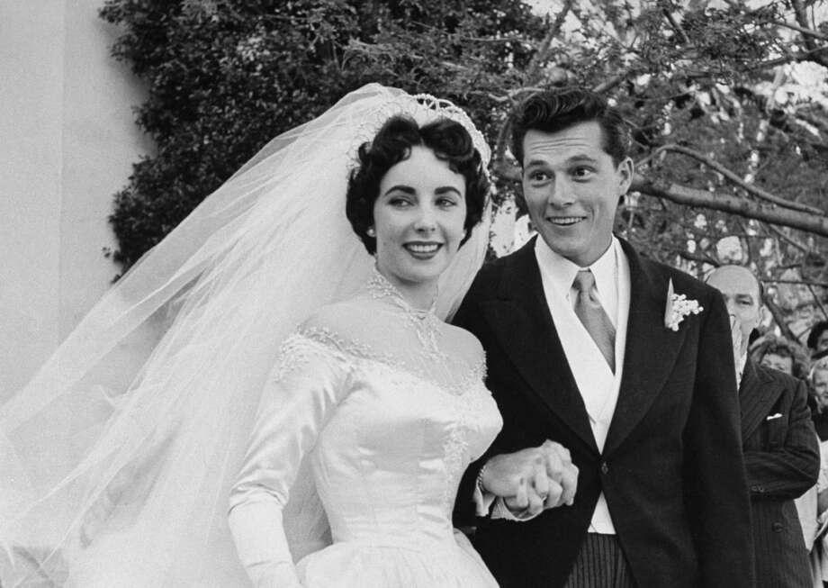 Actress Elizabeth Taylor wearing beautiful satin wedding gown (cost $1,500, a gift from MGM studios) holding hands w. her husband Nicky Hilton outside church after their wedding ceremony.  (Photo by Ed Clark//Time Life Pictures/Getty Images)