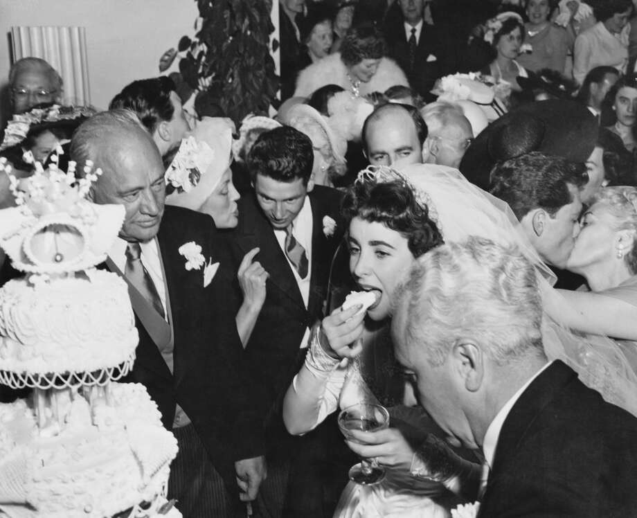 Elizabeth Taylor eating wedding cake at her wedding to Nicky Hilton, 6th May 1950. Her new father-in-law Conrad Hilton looks on and her father, art dealer Francis Taylor, stands next to her. (Photo by Archive Photos/Getty Images)
