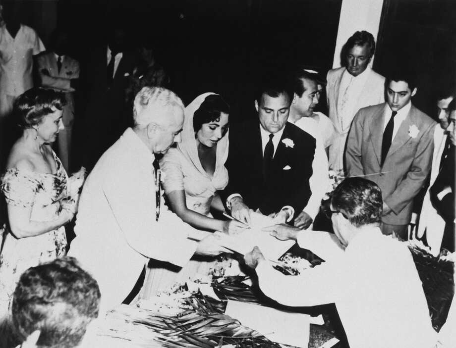 Actress Elizabeth Taylor and Mike Todd signing the register on their wedding day, 2nd February 1957, Acapulco. Her parents Francis and Sara are on the left and her brother Howard looks on (right). Taylor's marriage to Todd (whom she called one of the great loves of her life) ended with Todd's tragic death in a plane crash in 1958. The couple had a daughter together, Liza Todd. (Photo by Archive Photos/Getty Images)