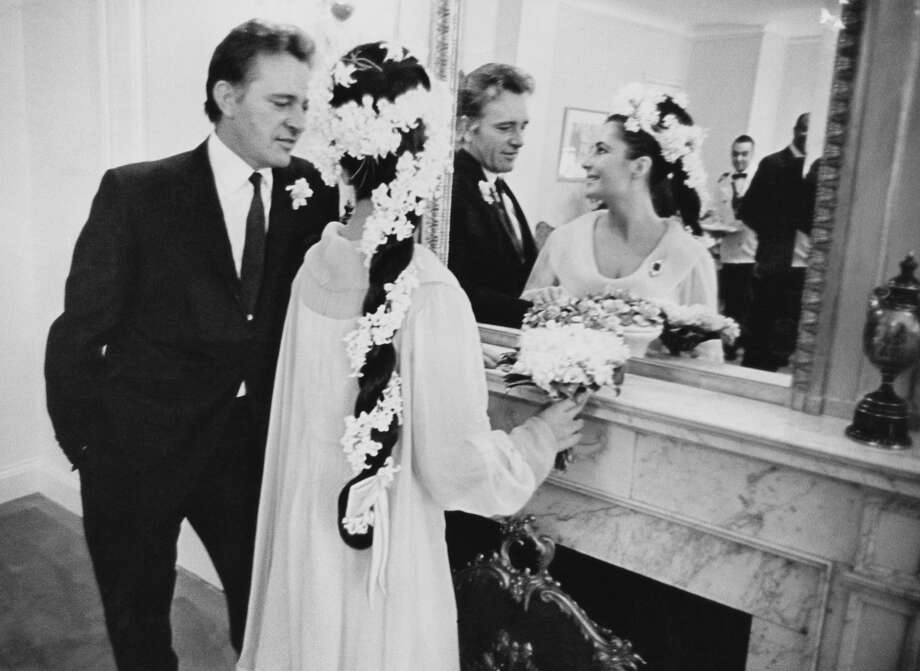 "15th March 1964:  film stars Elizabeth Taylor (1932 - 2011) and Richard Burton (1925 - 1984) at their first wedding in Montreal, Canada. The ""sunflower yellow"" dress was by 'Cleopatra"" costumer Irene Sharaff (Photo by William Lovelace/Evening Standard/Getty Images)"