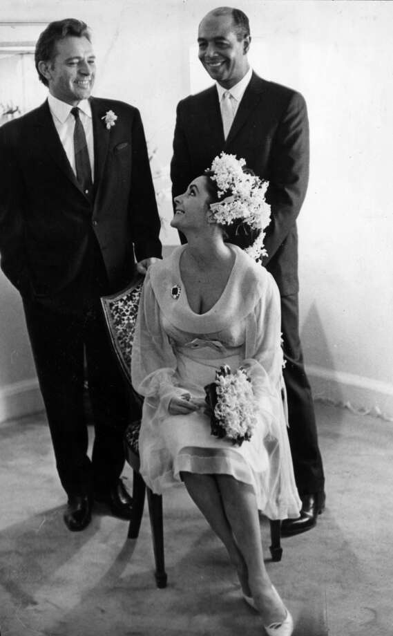 15th March 1964:  Elizabeth Taylor (1932 - 2011) and Richard Burton (1925 - 1984, left) at their first wedding in Montreal, Canada. With them is their best man Jim Benton.  Taylor and Burton adopted a daughter, Maria Burton, together from East Germany. (Photo by William Lovelace/Evening Standard/Getty Images)