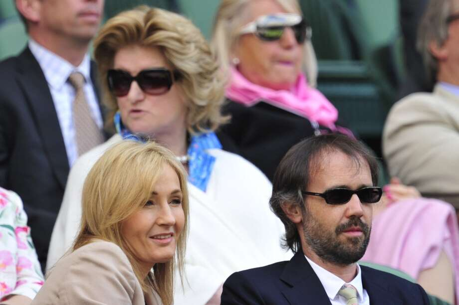 British author J K Rowling sits watching the action on centre court with her husband Neil Murray during play on day two of the 2013 Wimbledon Championships tennis tournament.