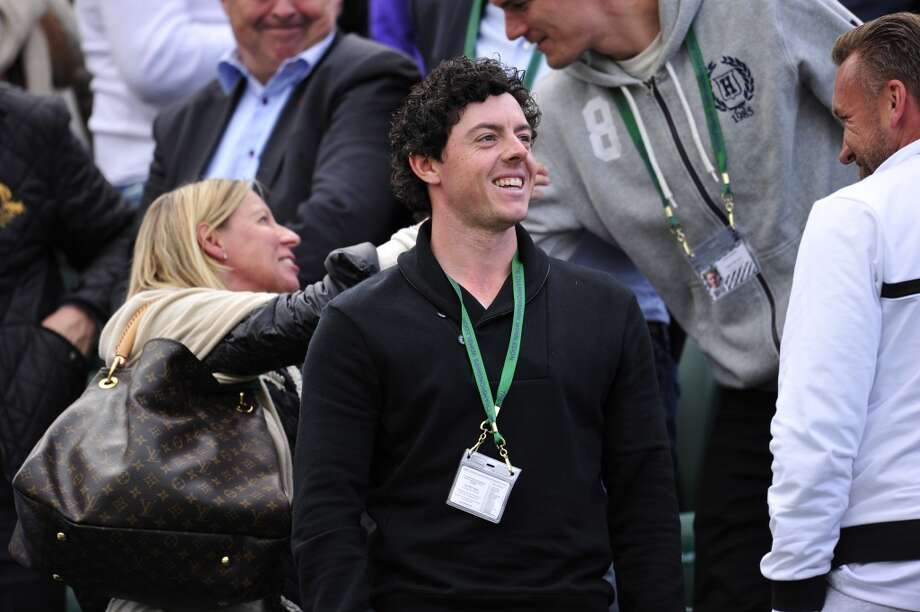 Northern Irish golf player Rory McIlroy stands in the crowd to watch his girlfriend Denmark's Caroline Wozniacki play against Spain's Estrella Cabeza Candela during their women's first round match on day one of the 2013 Wimbledon Championships.