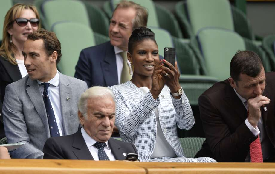 Retired British athlete Denise Lewis (C) takes a picture with her phone in the box at centre court ahead of the men's first round match between Britain's Andy Murray and Germany's Benjamin Becker on day one of the 2013 Wimbledon Championships.