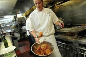 Chef Jason Dady tosses wings in his Thai red curry sauce at Bin 555 on Tuesday, May 14, 2013.