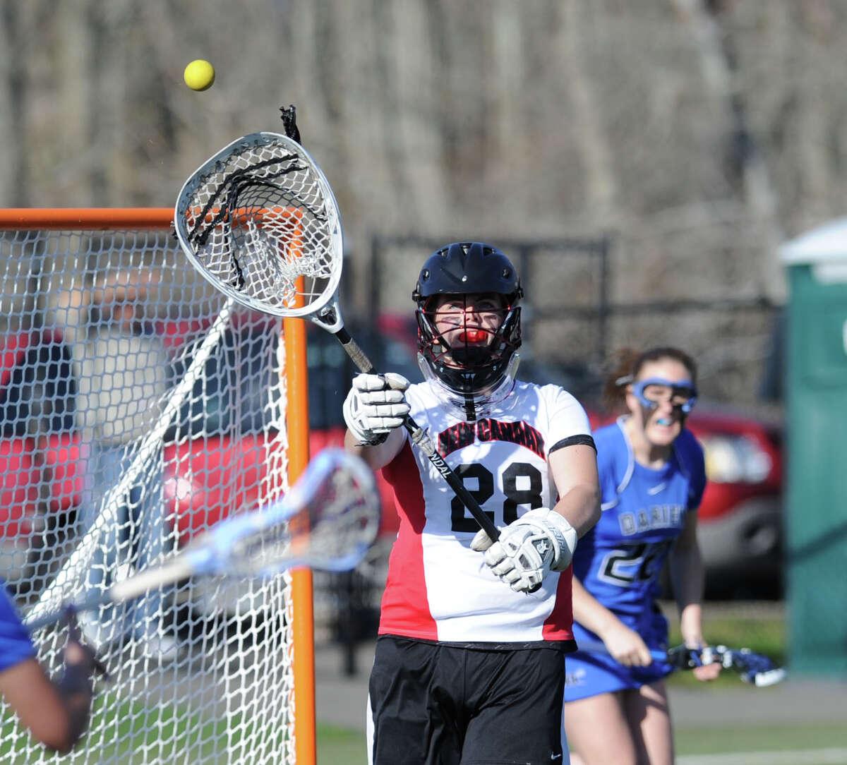 Goalie Liz O'Sullivan # 28 of New Canaan passes during the girls high school lacrosse match between New Canaan High School and Darien High School at New Canaan, Thursday, April 25, 2013. Darien won the match, 14-7.