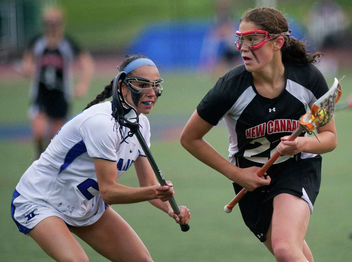 New Canaan's Olivia Hompe carries the ball during Friday's girls lacrosse FCIAC Championship game against Darien at Brien McMahon High School in Norwalk, Conn., on May 24, 2013.