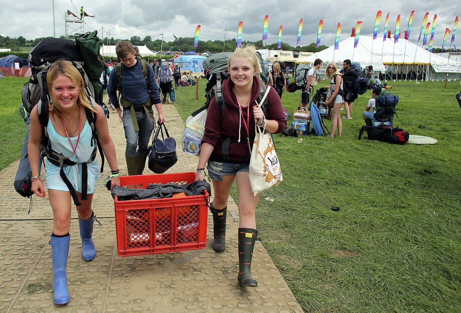 People arrive at the Glastonbury Festival of Contemporary Performing Arts site at Worthy Farm, in Pilton at Worthy Farm, Pilton on June 26, 2013 near Glastonbury, England.  Gates opened today at the Somerset diary farm that will be playing host to one of the largest music festivals in the world and this year features headline acts Artic Monkeys, Mumford and Sons and the Rolling Stones. Tickets to the event which is now in its 43rd year sold out in minutes and that was before any of the headline acts had been confirmed. The festival, which started in 1970 when several hundred hippies paid 1 GBP to watch Marc Bolan, now attracts more than 175,000 people over five days. Photo: Matt Cardy, Getty Images / 2013 Getty Images