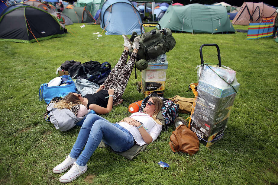 People relax in front of newly erected tents at the Glastonbury Festival of Contemporary Performing Arts site at Worthy Farm, in Pilton at Worthy Farm, Pilton on June 26, 2013 near Glastonbury, England.  Gates opened today at the Somerset diary farm that will be playing host to one of the largest music festivals in the world and this year features headline acts Arctic Monkeys, Mumford and Sons and the Rolling Stones. Tickets to the event which is now in its 43rd year sold out in minutes and that was before any of the headline acts had been confirmed. The festival, which started in 1970 when several hundred hippies paid 1 GBP to watch Marc Bolan, now attracts more than 175,000 people over five days. Photo: Matt Cardy, Getty Images / 2013 Getty Images