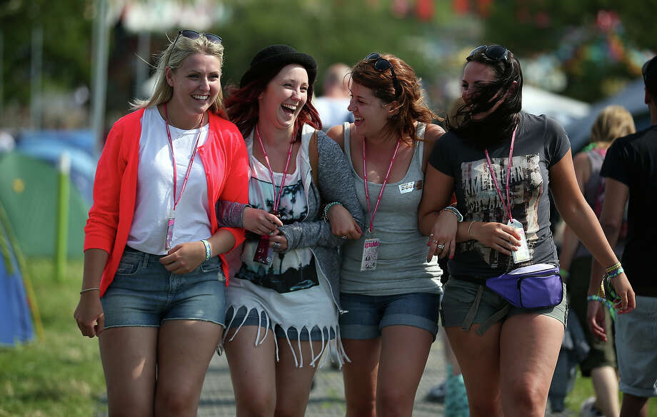 (L-R) Gemma Wigmore, Emily Golding, Leanne Scull and Charlotte Wigmore, all from Bristol laugh as they walk around the Glastonbury Festival of Contemporary Performing Arts site at Worthy Farm, Pilton on June 26, 2013 near Glastonbury, England. Gates opened today at the Somerset diary farm that will be playing host to one of the largest music festivals in the world and this year features headline acts Arctic Monkeys, Mumford and Sons and the Rolling Stones. Tickets to the event which is now in its 43rd year sold out in minutes and that was before any of the headline acts had been confirmed. The festival, which started in 1970 when several hundred hippies paid 1 GBP to watch Marc Bolan, now attracts more than 175,000 people over five days. Photo: Matt Cardy, Getty Images / 2013 Getty Images