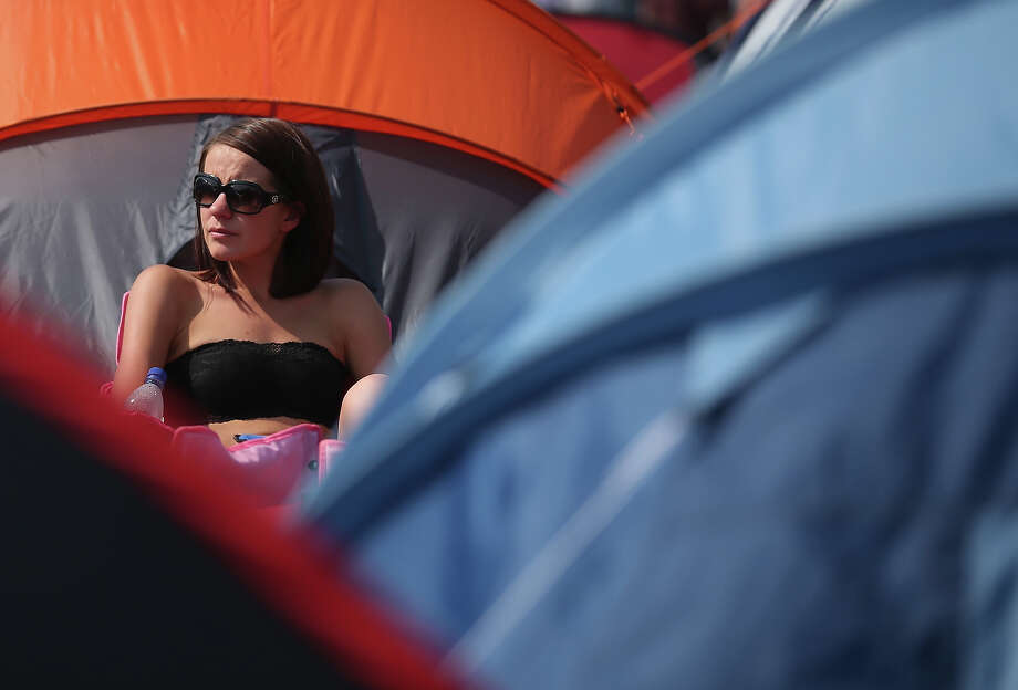 Gemma Hall from London sits in the sun at the Glastonbury Festival of Contemporary Performing Arts site at Worthy Farm, Pilton on June 26, 2013 near Glastonbury, England. Gates opened today at the Somerset diary farm that will be playing host to one of the largest music festivals in the world and this year features headline acts Arctic Monkeys, Mumford and Sons and the Rolling Stones. Tickets to the event which is now in its 43rd year sold out in minutes and that was before any of the headline acts had been confirmed. The festival, which started in 1970 when several hundred hippies paid 1 GBP to watch Marc Bolan, now attracts more than 175,000 people over five days. Photo: Matt Cardy, Getty Images / 2013 Getty Images