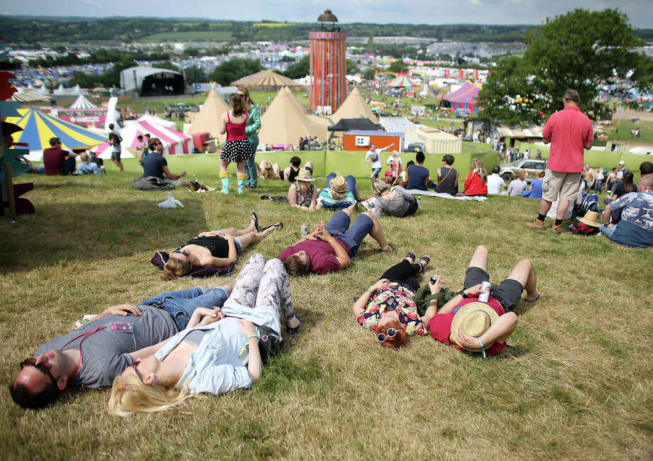 People lie in the sun at the Glastonbury Festival of Contemporary Performing Arts site at Worthy Farm, Pilton on June 26, 2013 near Glastonbury, England.  Gates opened today at the Somerset diary farm that will be playing host to one of the largest music festivals in the world and this year features headline acts Arctic Monkeys, Mumford and Sons and the Rolling Stones. Tickets to the event which is now in its 43rd year sold out in minutes and that was before any of the headline acts had been confirmed. The festival, which started in 1970 when several hundred hippies paid 1 GBP to watch Marc Bolan, now attracts more than 175,000 people over five days. Photo: Matt Cardy, Getty Images / 2013 Getty Images