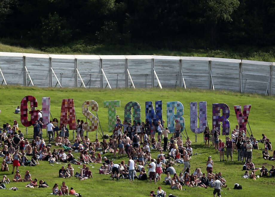 People sit below the Glastonbury name sign at the Glastonbury Festival of Contemporary Performing Arts site at Worthy Farm, Pilton on June 26, 2013 near Glastonbury, England. Gates opened today at the Somerset diary farm that will be playing host to one of the largest music festivals in the world and this year features headline acts Arctic Monkeys, Mumford and Sons and the Rolling Stones. Tickets to the event which is now in its 43rd year sold out in minutes and that was before any of the headline acts had been confirmed. The festival, which started in 1970 when several hundred hippies paid 1 GBP to watch Marc Bolan, now attracts more than 175,000 people over five days. Photo: Matt Cardy, Getty Images / 2013 Getty Images