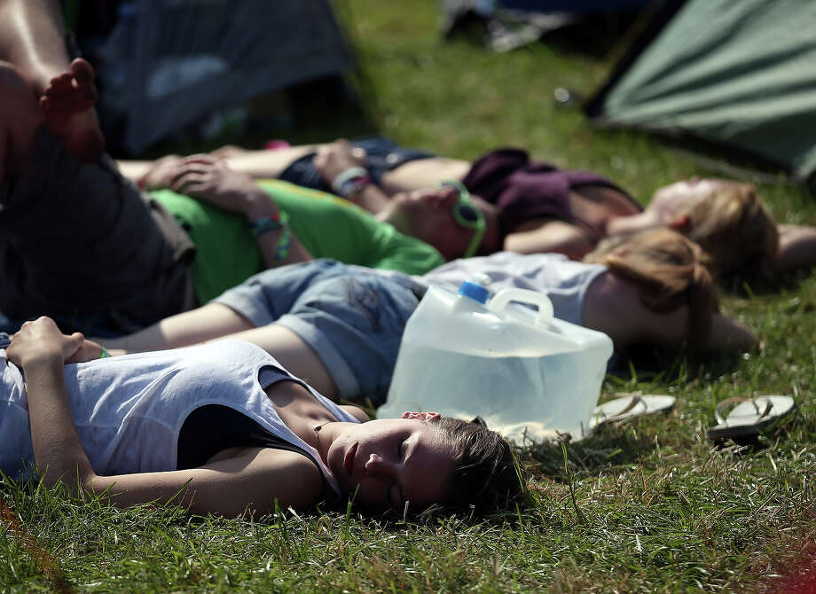 People lie in the sun besides their tents at the Glastonbury Festival of Contemporary Performing Arts site at Worthy Farm, Pilton on June 26, 2013 near Glastonbury, England. Gates opened today at the Somerset diary farm that will be playing host to one of the largest music festivals in the world and this year features headline acts Arctic Monkeys, Mumford and Sons and the Rolling Stones. Tickets to the event which is now in its 43rd year sold out in minutes and that was before any of the headline acts had been confirmed. The festival, which started in 1970 when several hundred hippies paid 1 GBP to watch Marc Bolan, now attracts more than 175,000 people over five days. Photo: Matt Cardy, Getty Images / 2013 Getty Images