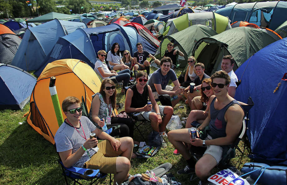 GLASTONBURY, ENGLAND - JUNE 26:  A group of friends sit with the recently erected tents at the Glastonbury Festival of Contemporary Performing Arts site at Worthy Farm, Pilton on June 26, 2013 near Glastonbury, England. Gates opened today at the Somerset diary farm that will be playing host to one of the largest music festivals in the world and this year features headline acts Artic Monkeys, Mumford and Sons and the Rolling Stones. Tickets to the event which is now in its 43rd year sold out in minutes and that was before any of the headline acts had been confirmed. The festival, which started in 1970 when several hundred hippies paid 1 GBP to watch Marc Bolan, now attracts more than 175,000 people over five days. Photo: Matt Cardy, Getty Images / 2013 Getty Images