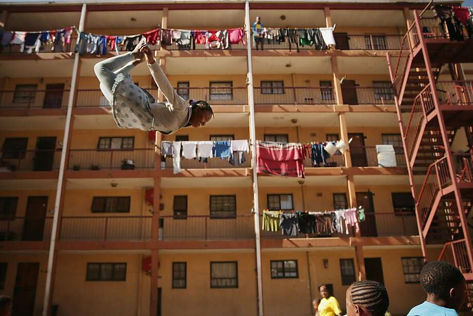 Alley oop: Twelve-year-old Phaphama Nxumalo flies like Peter Pan in an alley of tenements in 