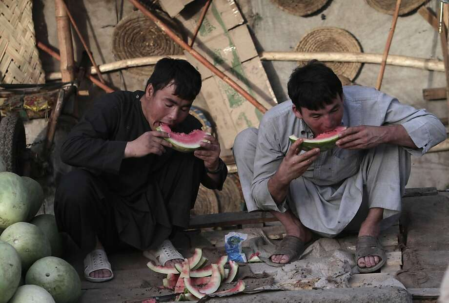 Another slice, fellas?These two look like they could finish a whole watermelon in one   sitting. (Kabul.) Photo: Rahmat Gul, Associated Press