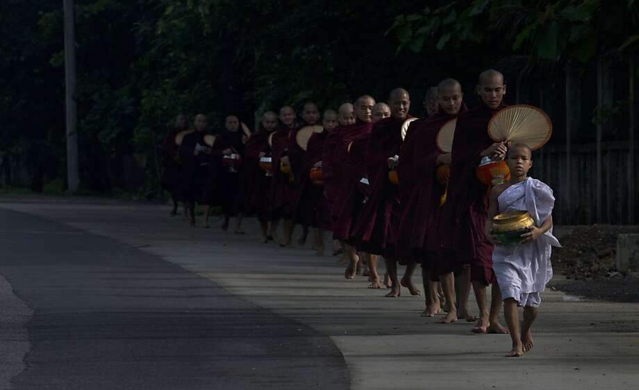 All your monks in a row: Buddhist monks collecting alms are led single-file by a novice in Yangon, Myanmar. Photo: Gemunu Amarasinghe, Associated Press