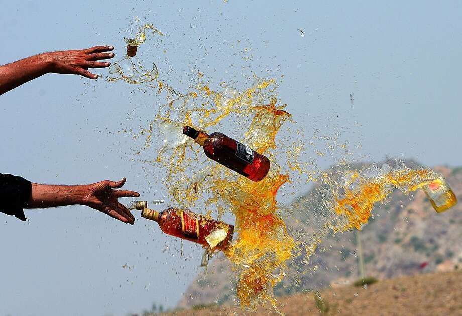 How could they do this to a 12-year-old? A Pakistani soldier destroys perfectly good bottles of scotch and bourbon in the Shahkas area of the Jamrud Khyber Agency, one of the nation's federally administered tribal areas. Officials smashed the whiskey as part of the International Anti-Drug Day observance. Photo: A Majeed, AFP/Getty Images