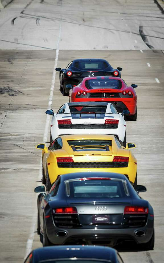 A selection of high-end sports race cars wait to be driven at the Exotic Driving Experience at MSR Houston race track Photo: Michael Paulsen, Staff / © 2013 Houston Chronicle