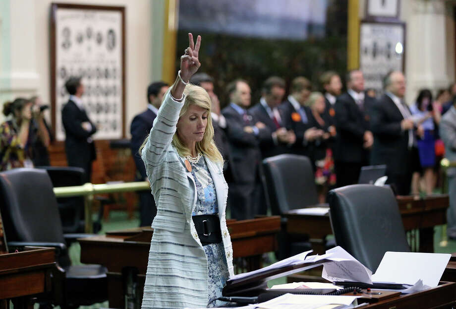 Fort Worth Senator Wendy Davis signals a no vote after she filibusters in an effort to cause abortion legislation to die without a vote on the floor of the Senate Tuesday, June 25, 2013. Photo: TOM REEL, San Antonio Express-News / San Antonio Express-News
