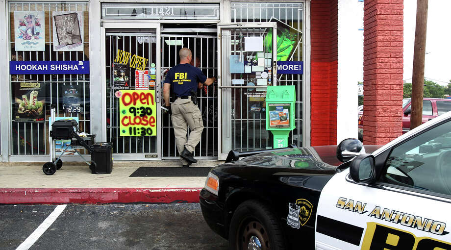 An F.B.I. agent enters the Hang Ten store Wednesday morning June 26, 2013 at 11,421 West Avenue. The F.B.I. and other federal agencies made stops at several stores around San Antonio that sell synthetic marijuana. A press conference is expected at 3:00 p.m. that should provide more details. Photo: John Davenport, San Antonio Express-News / SAN ANTONIO EXPRESS-NEWS