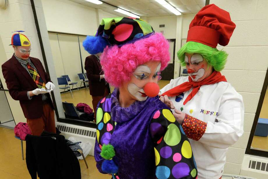 Briana O'Connor, center, gets an assist from fellow student Molly McIver in getting her costume on during the clowning class at The College of St. Rose College in Albany.  (Skip Dickstein / Times Union) Photo: SKIP DICKSTEIN / 00021812A