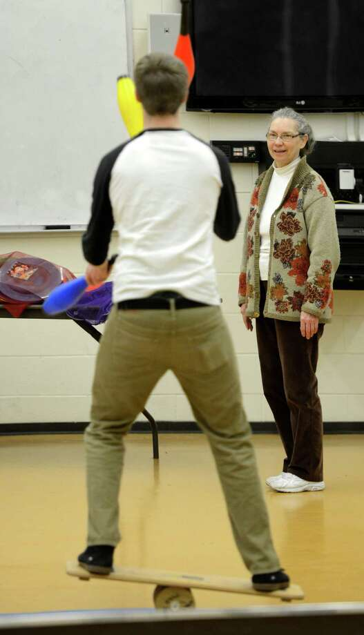 Instructor Ann Neilson, right watches student Kevin Bohen juggle on the balance board during the clowning class at St. Rose in Albany.  (Skip Dickstein / Times Union) Photo: SKIP DICKSTEIN / 00021812A