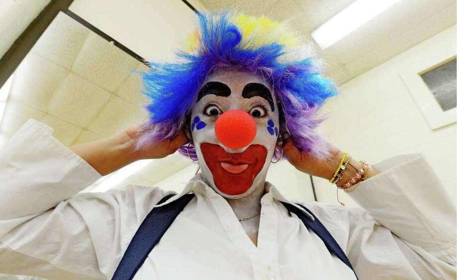 Jessica Lopez pulls on her wig during the clowning class at The College of St. Rose College in Albany.  (Skip Dickstein / Times Union) Photo: SKIP DICKSTEIN / 00021812A