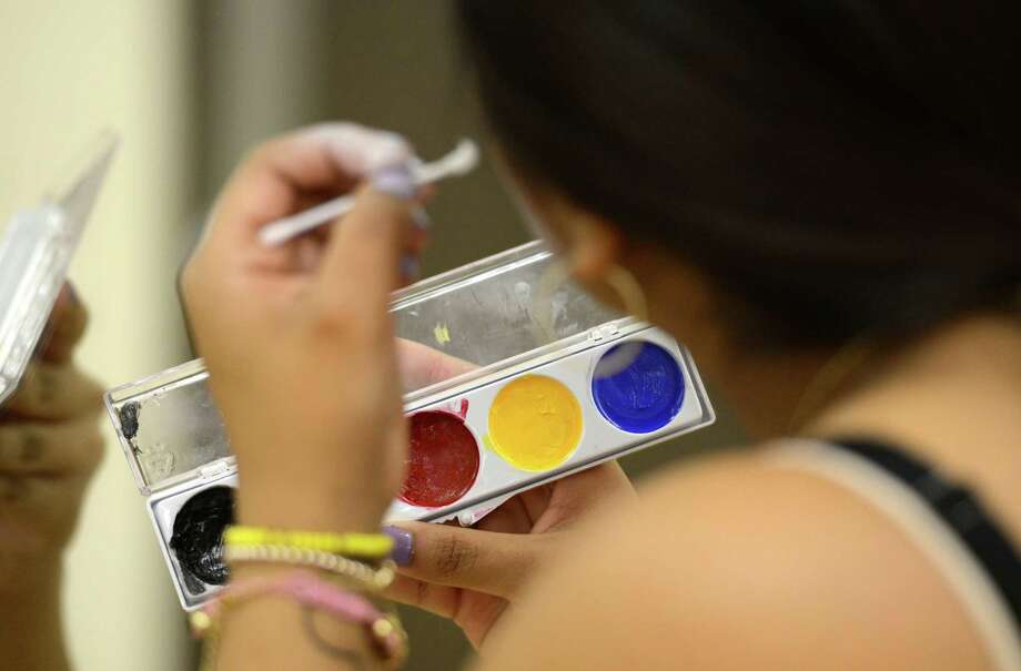 Jessica Lopez applies makeup during the clowning class at St. Rose in Albany.  (Skip Dickstein / Times Union) Photo: SKIP DICKSTEIN / 00021812A