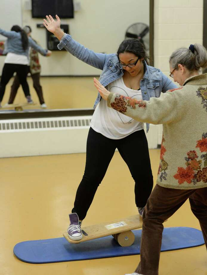 Student Jessica Lopez gets training on the balance board from instructor Ann Neilson, right, during the clowning class at St. Rose in Albany.  (Skip Dickstein / Times Union) Photo: SKIP DICKSTEIN / 00021812A