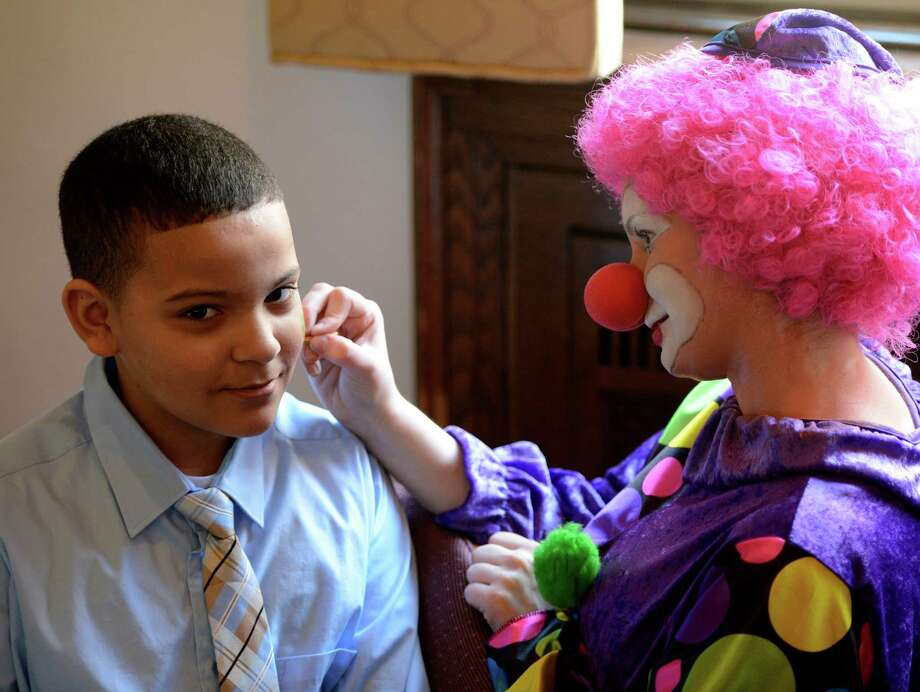 Briana O'Connor applies face paint to Tamir Davis while on her clowning assignment as part of the class at St. Rose in Albany.  (Skip Dickstein / Times Union) Photo: SKIP DICKSTEIN / 00021812A