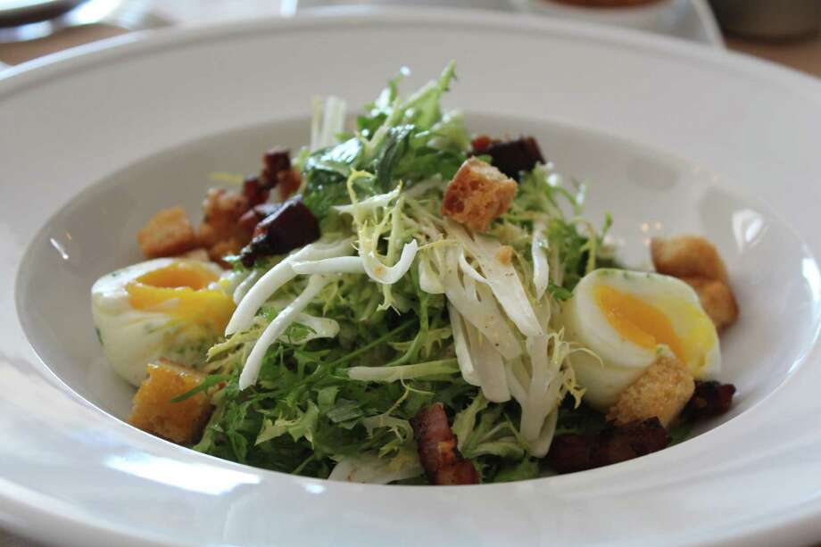 The frisée salad at Minnie's Tavern and Rye House is topped with lardons, poached eggs and vinaigrette. Photo: Jennifer McInnis / San Antonio Express-News