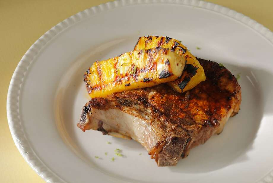 Spiced Pork Chops With Grilled Pineapple: Find pineapple that is firm but sweet - it should hold its shape when grilled. Click here for the recipe.  Photo: Craig Lee