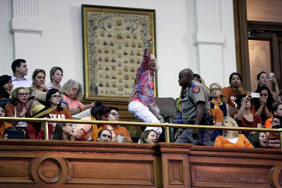 A spectator jumps up to leave after Fort Worth Senator Wendy Davis is stopped in her filibuster in an effort to cause abortion legislation to die without a vote on the floor of the Senate Tuesday, June 25, 2013. Photo: TOM REEL