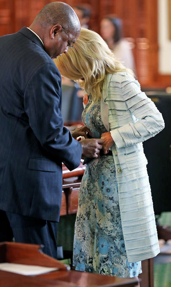 Senator Rodney Ellis D-Houston helps with a back brace as Fort Worth Senator Wendy Davis filibusters in an effort to cause abortion legislation to die without a vote on the floor of the Senate Tuesday, June 25, 2013. Photo: TOM REEL