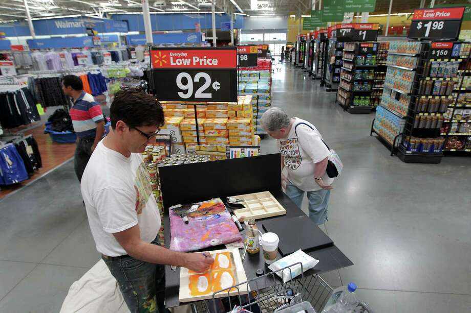 "Nationally-known artist Brendan O'Connell left, who's become famous as ""Walmart's Warhol,"" paints as Nancy Fleming right, looks on during O'Connell's visit to the Heights Walmart, O'Connell uses the people and products in Walmart stores to represent the American consumer experience Wednesday, June 26, 2013, in Houston. His oil paintings now sell for thousands of dollars, but there was a time store managers kicked him out when they caught O'Connell taking photos. ( James Nielsen / Houston Chronicle ) Photo: James Nielsen, Staff / © 2013  Houston Chronicle"