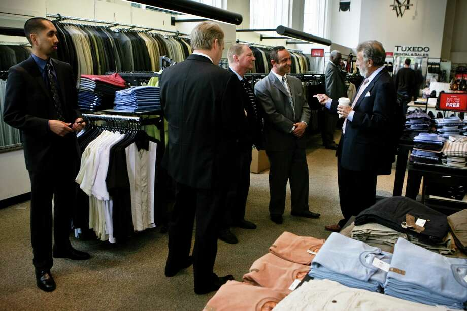 Men's Wearhouse CEO George Zimmer, far right, greets salesmens (from center right facing) Mike Emini, Tim Henning, as new CEO Douglas Ewert , back shown and store manager, Sani Tongol, far left looks on at the San Francisco's downtown store on Market St.  Zimmer will continue to be the company's spokesperson. (Photo by Vasna Wilson/Freelance) Photo: Vasna Wilson WilsonManish Tandon, Freelance / Vasna Wilson