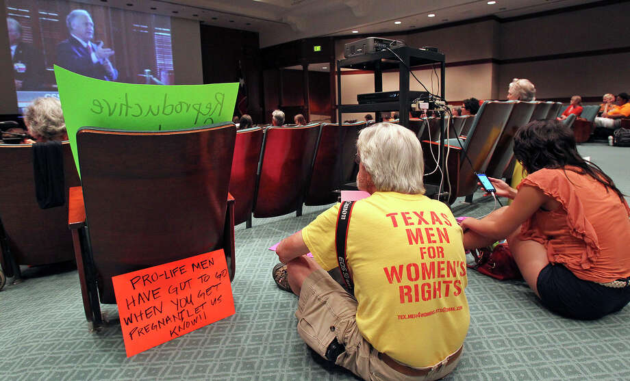 David Thomas rests with his signs on the floor of an auditorium being used as overflow for spectators as Fort Worth Senator Wendy Davis filibusters in an effort to cause abortion legislation to die without a vote on the floor of the Senate Tuesday, June 25, 2013. Photo: TOM REEL